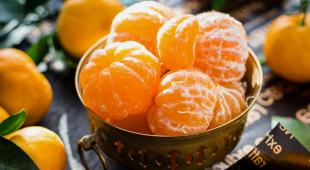 Peeled clementines or mandarin oranges in a brass bowl.