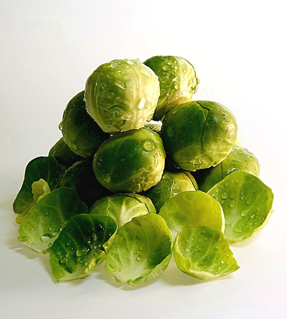 A small pyramid of fresh brussels sprouts doused in water.