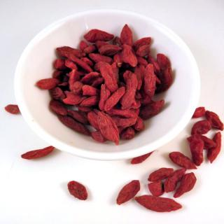 Dried red goji berries in a white bowl with a dew spilled to the side.