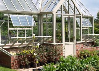 Aluminium-framed greenhouse with brick foundations.