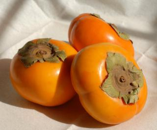Three persimmon fruits on a white tablecloth.