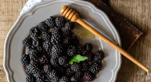 Blackberries in a plate with a dollup of honey.