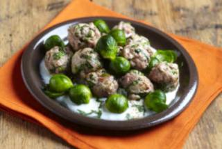 A plate of brussels sprouts with veal meatballs in cream sauce.