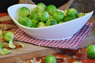 Steamed Brussel sprouts in a white dish on a homely table with cloth napkins.