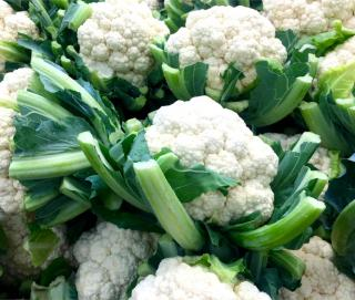 Cauliflower harvest stacked with cut leaf stalks.