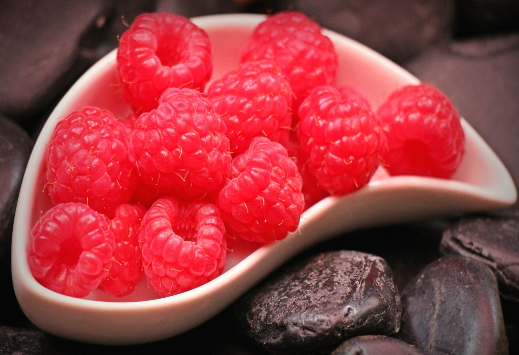 A saucer filled to the brim with red raspberries