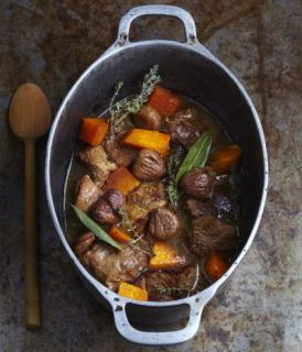 Iron pot with wood laddle filled with a delicious chestnut, lamb and squash Navarin stew.