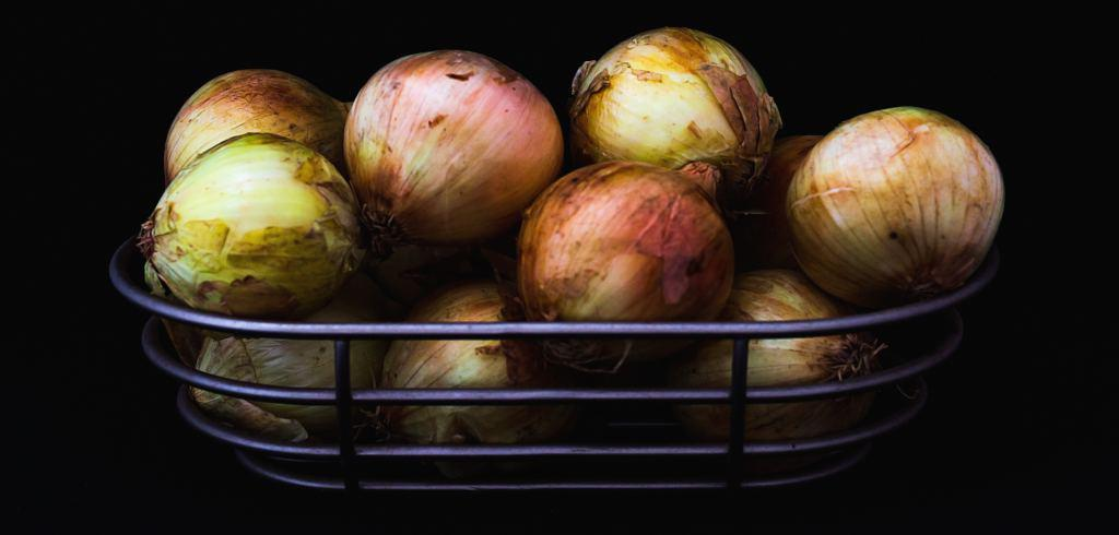 Harvested and dried onions in a steel rack for storage.