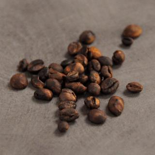 A handful of roasted coffee beans ready to be ground up and used in the garden.