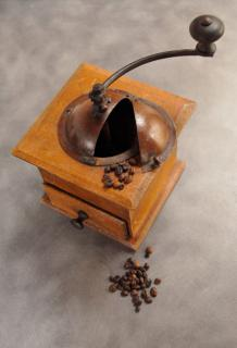 Coffee grinder, the old wooden manual type, and a few grains of coffee for preparing coffee grinds for the garden.