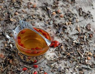 Goji berries steeped in water with an elegant spoon.
