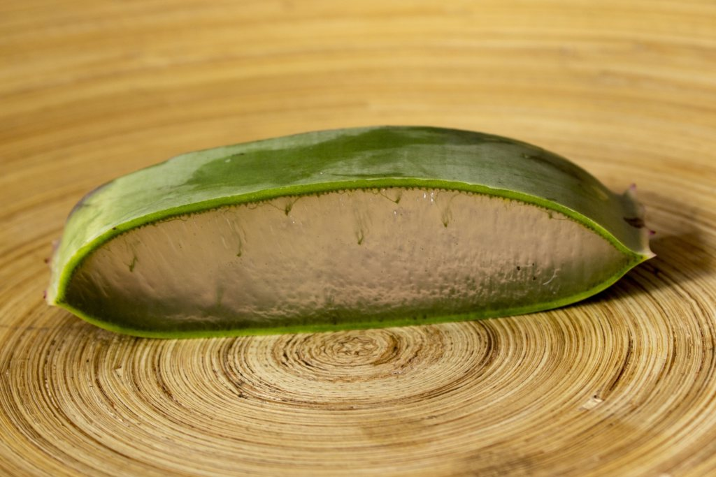 A slice of aloe vera on a wooden circular chopping board.