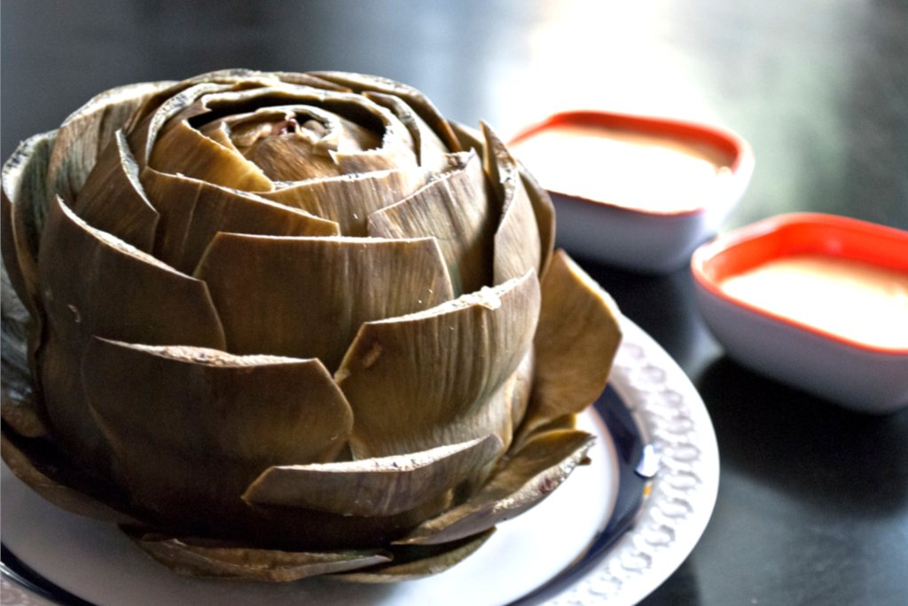 Artichoke with snipped leaves on a plate with sauces.