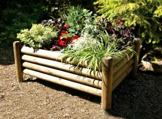 Raised garden bed made from round posts fastened together.