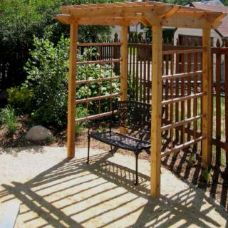 Small two-person seat pergola ready to welcome vine plants