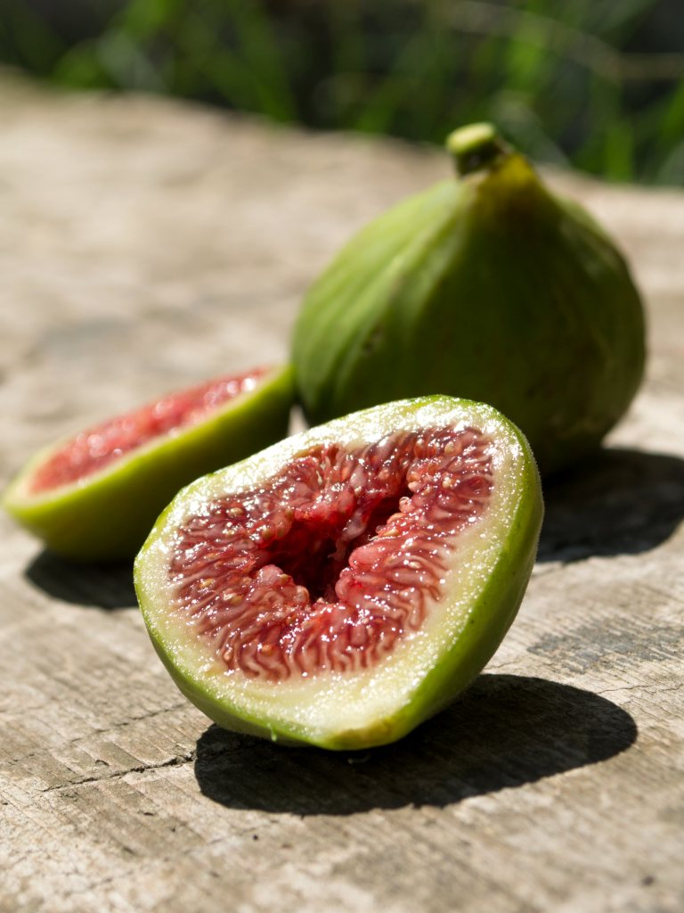 A ripe green fig sliced open on a wooden outdoor table.