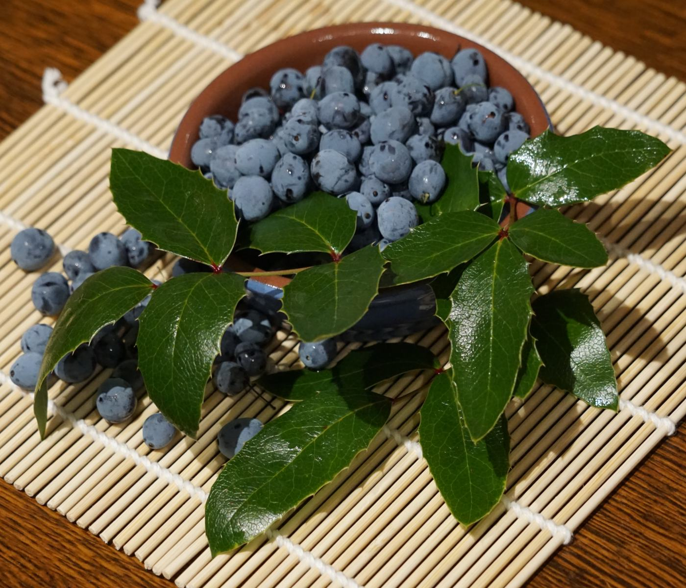 Bowl of Mahonia berries with leaves on wicker mat.