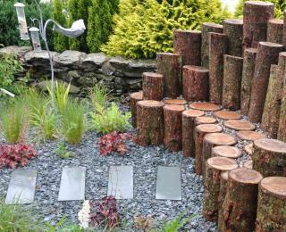 Slate mulch with stone path and log seat.