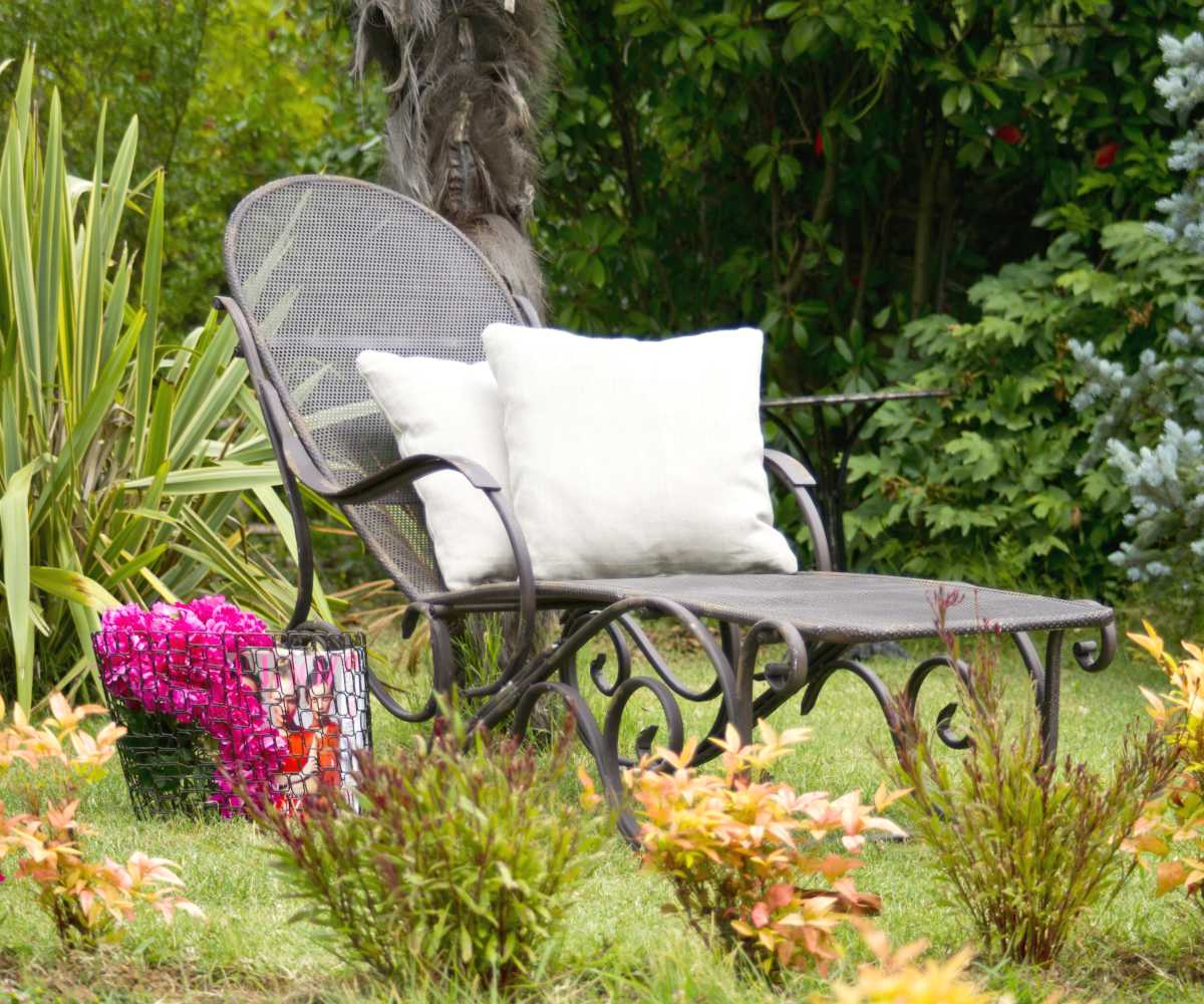 A lawn chair with comfortable pillows in an affordable garden setting.